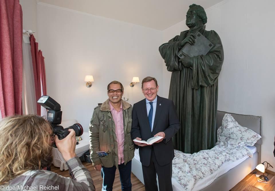 """Tatzu Nishi und Ministerpräsident Bodo Ramelow. Der Ministerpräsident sagte bei der Eröffnungsfeier: """"Luther und sein Denkmal in Eisenach seien zwar bekannt, werden aber kaum besonders wahrgenommen. Mit dem Kunstprojekt wird das Denkmal nun auf hochspannende Art wieder ins Bewusstsein zurückgeholt."""" Foto: Michael Reichel/dpa"""
